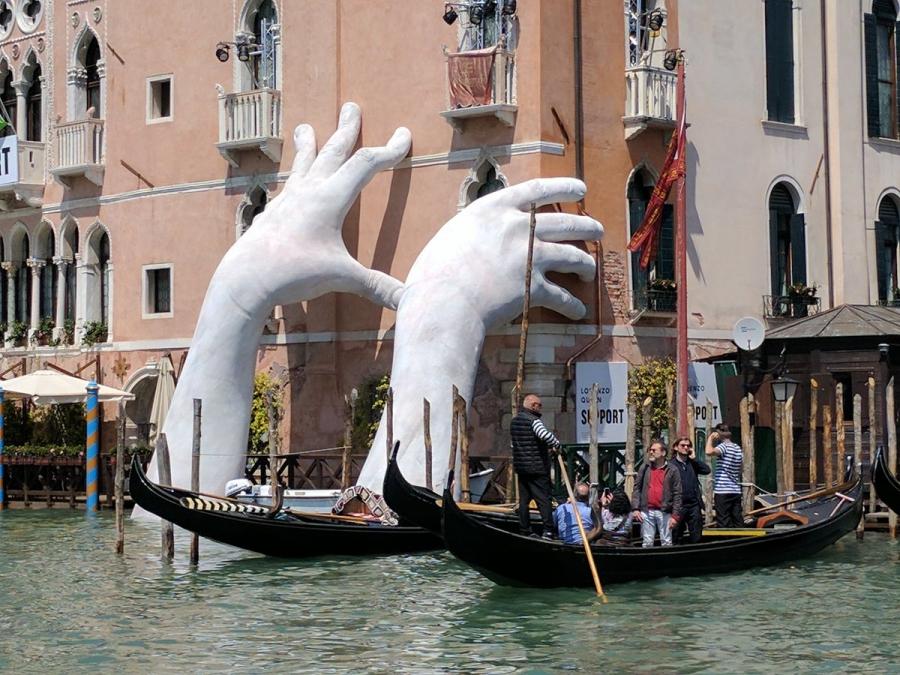 Гигантские руки поддерживают старинный отель в Венеции